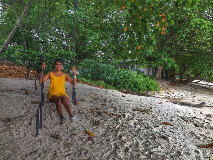 Portrait of woman sitting on swing at shore of beach