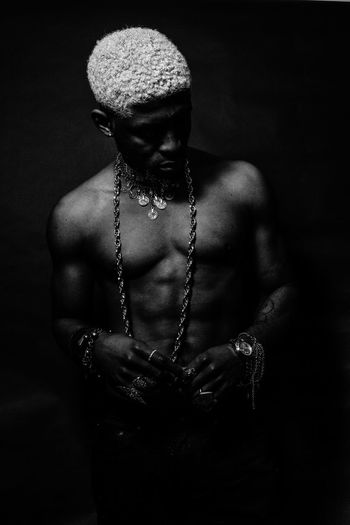 Close-up of shirtless man wearing jewelry against black background