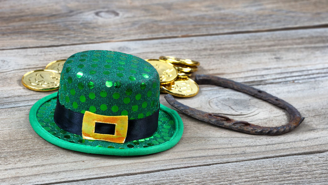 Lucky green hat, horseshoe and gold coins for St Patrick on rustic wooden boards in close up view Gold Green Color Hat Holiday Horseshoe Luck St Patrick's Day Wood Close-up Coin Irish St Patrick