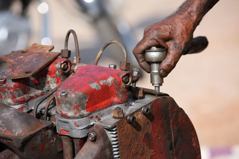 Close-up of man hand working on rusty machinery