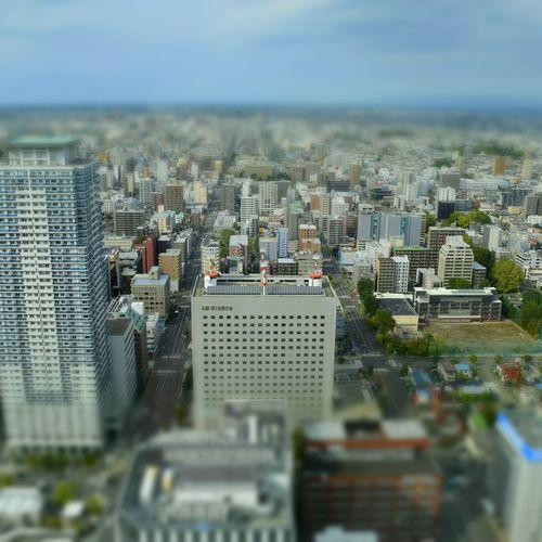 Tilt-shift image of cityscape against sky