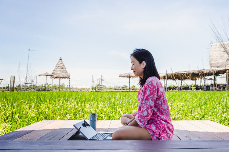 Side view of woman sitting outdoors against sky