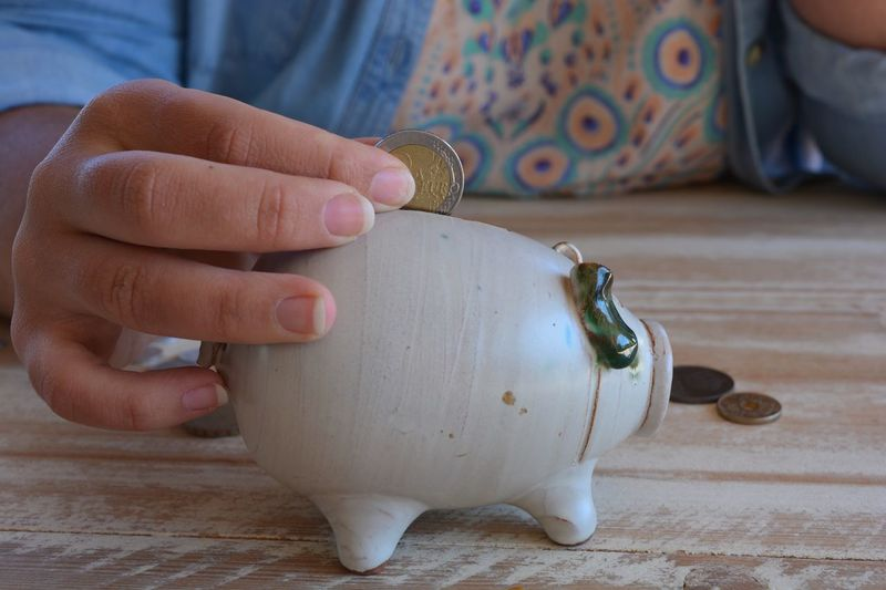 Midsection Of Woman Inserting Coin In Piggy Bank On Table