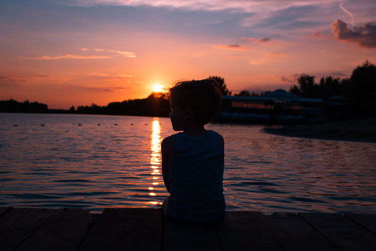 Rear view of boy sitting at beach against sky during sunset