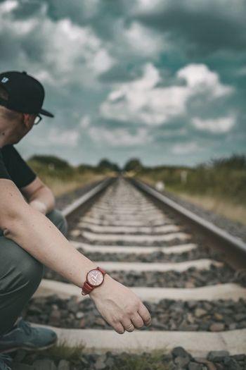 Man skateboarding on railroad track against sky