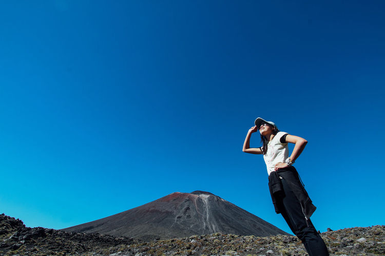 Low angle view of woman standing against clear blue sky