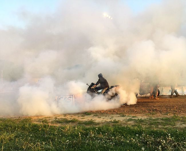 Man Emitting Smoke Through Motorcycle On Field