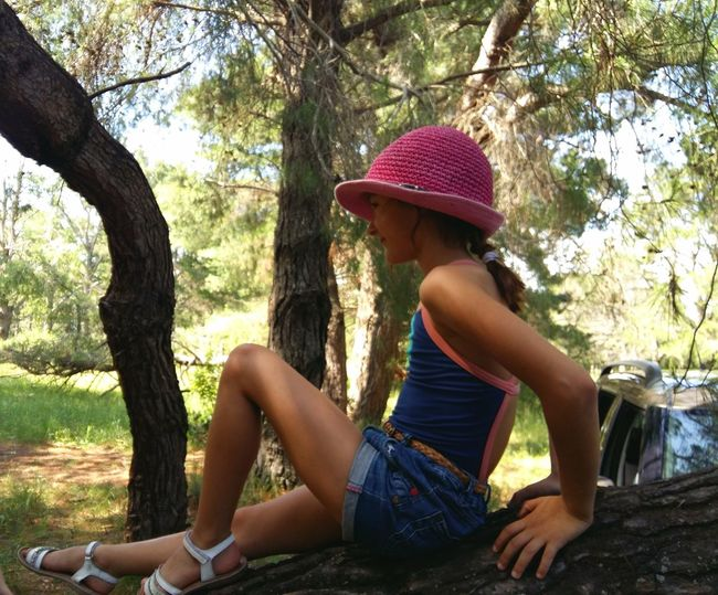 Girl sitting on tree in park