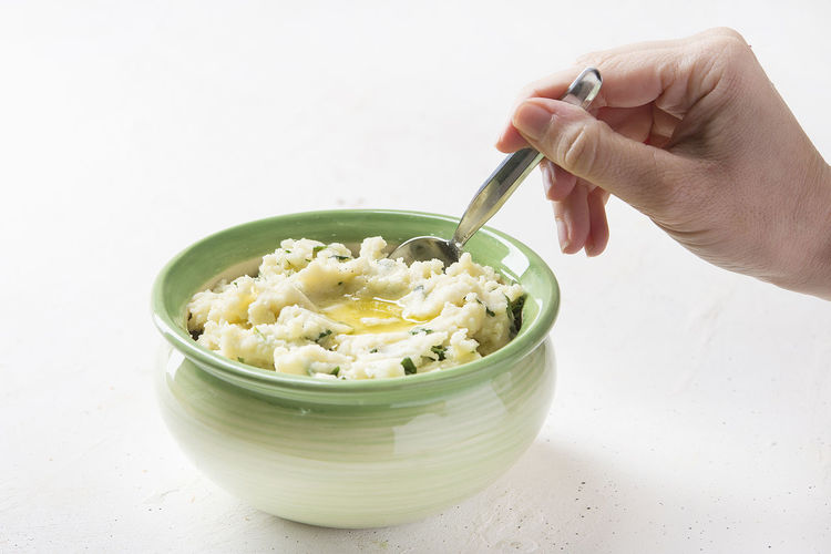 Midsection of person holding ice cream in bowl on table