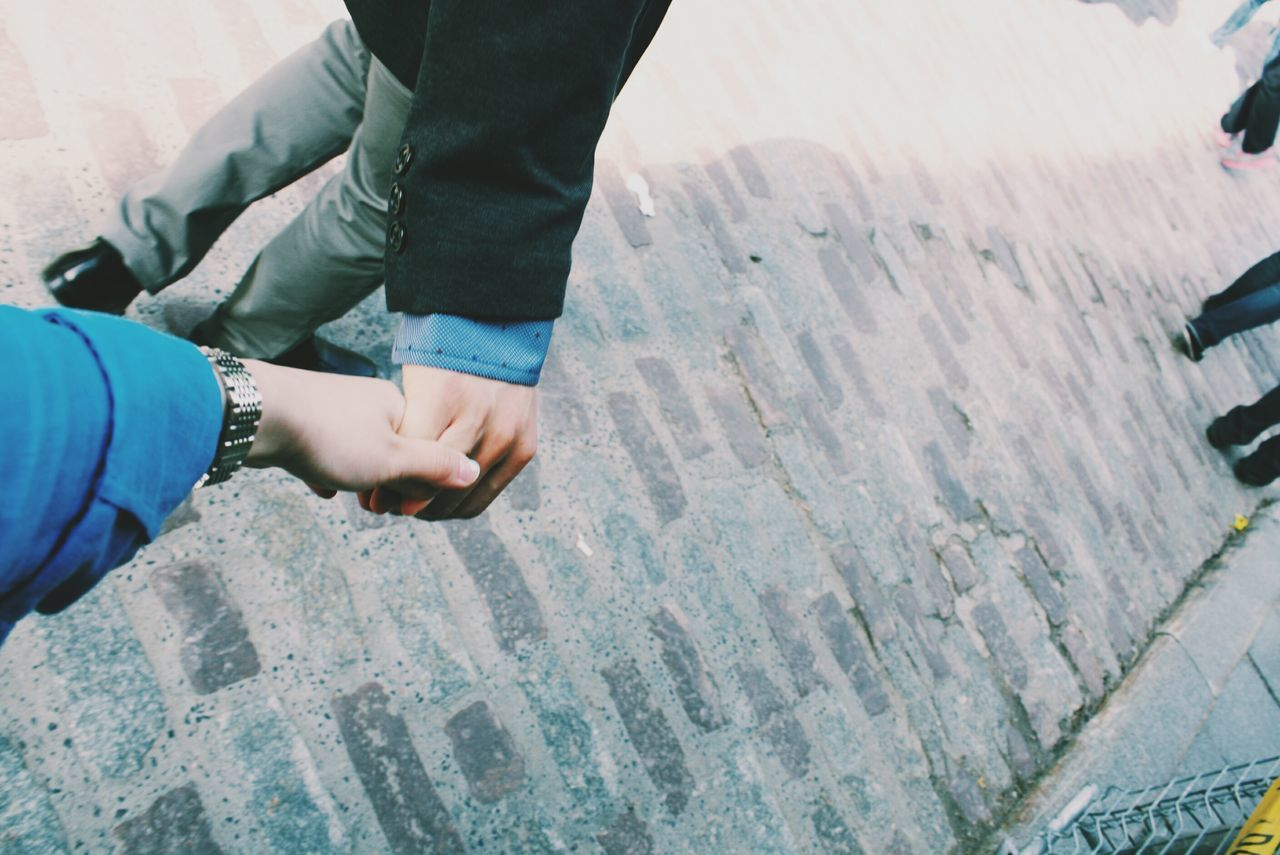 High angle view of couple holding hands on street
