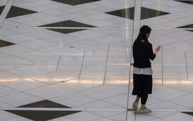 Rear view of woman standing on tiled floor