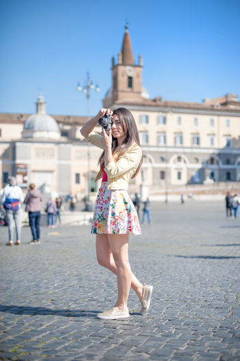 Full Length Of Beautiful Woman Photographing By Historic Building Against Sky