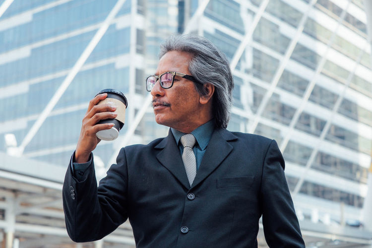 Businessman having coffee against office building