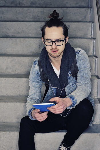 Young student using ipad 20s Casual Clothing Checking Mails Communication Confidence  Day Eyeglasses  Front View Internet Ipad Jacket Leisure Activity Lifestyles Men Portrait Student Student Life Tablet Wireless Technology Young Men