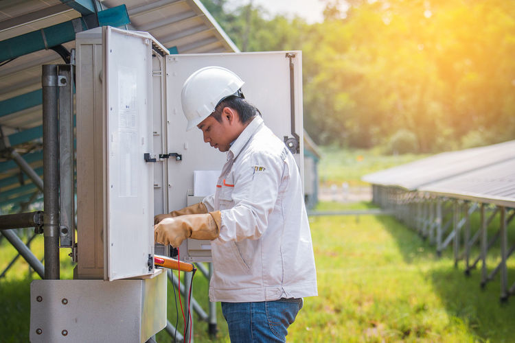 an engineer working on checking and maintenance equipment in solar power plant Array Check Data Electrician  Engineer Equipment Green Green Energy Industry Maintenance Meter - Instrument Of Measurement Photovoltaic Plant Power Safty Solar Energy Sunny Day Technician Technology Tool Voltage Working Hard World