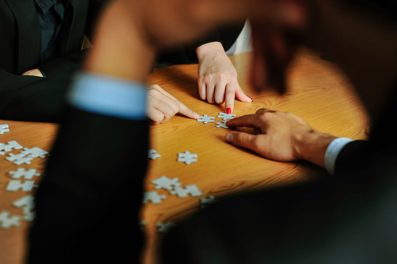 Midsection Playing Jigsaw Puzzle On Table