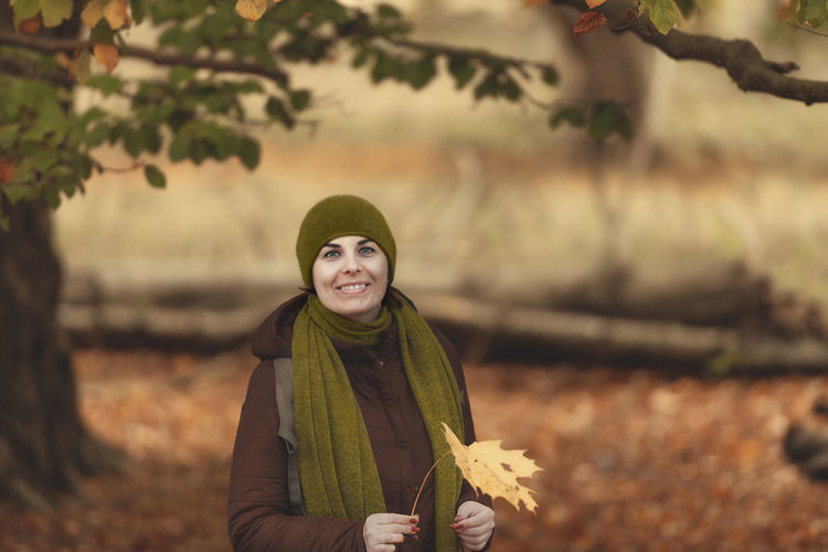 Portrait of smiling woman holding autumn leaf standing at park