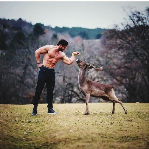 Shirtless man with muscular build standing by deer on field