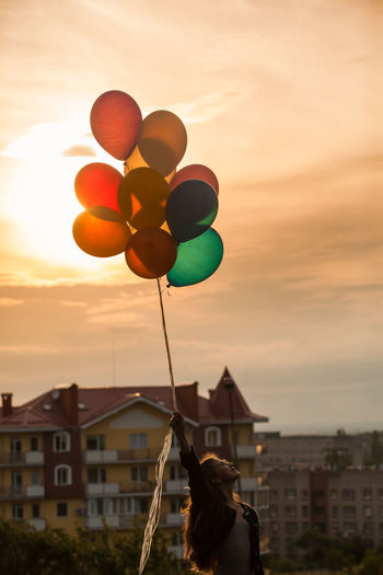 Rear view of silhouette person holding balloons against sky during sunset