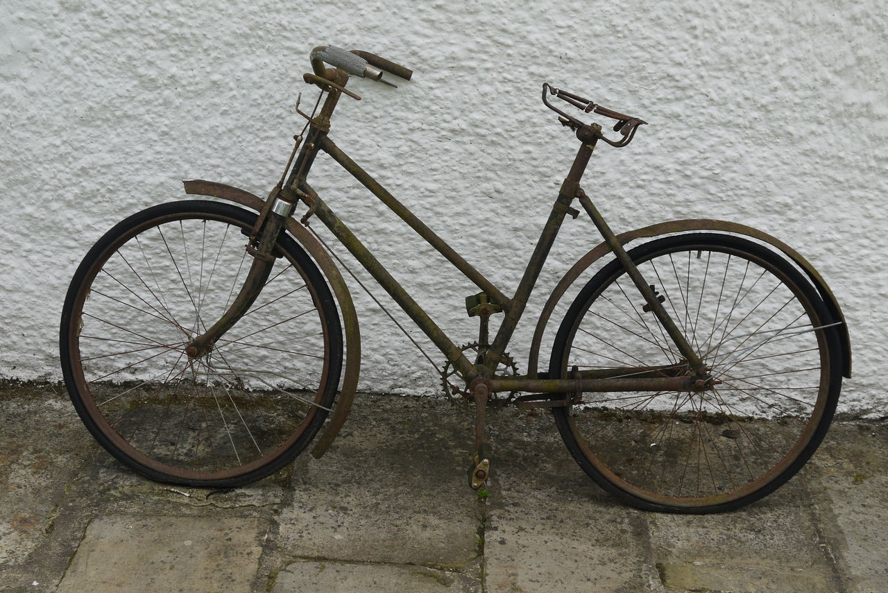 Abandoned Bicycle On Sidewalk Against White Wall