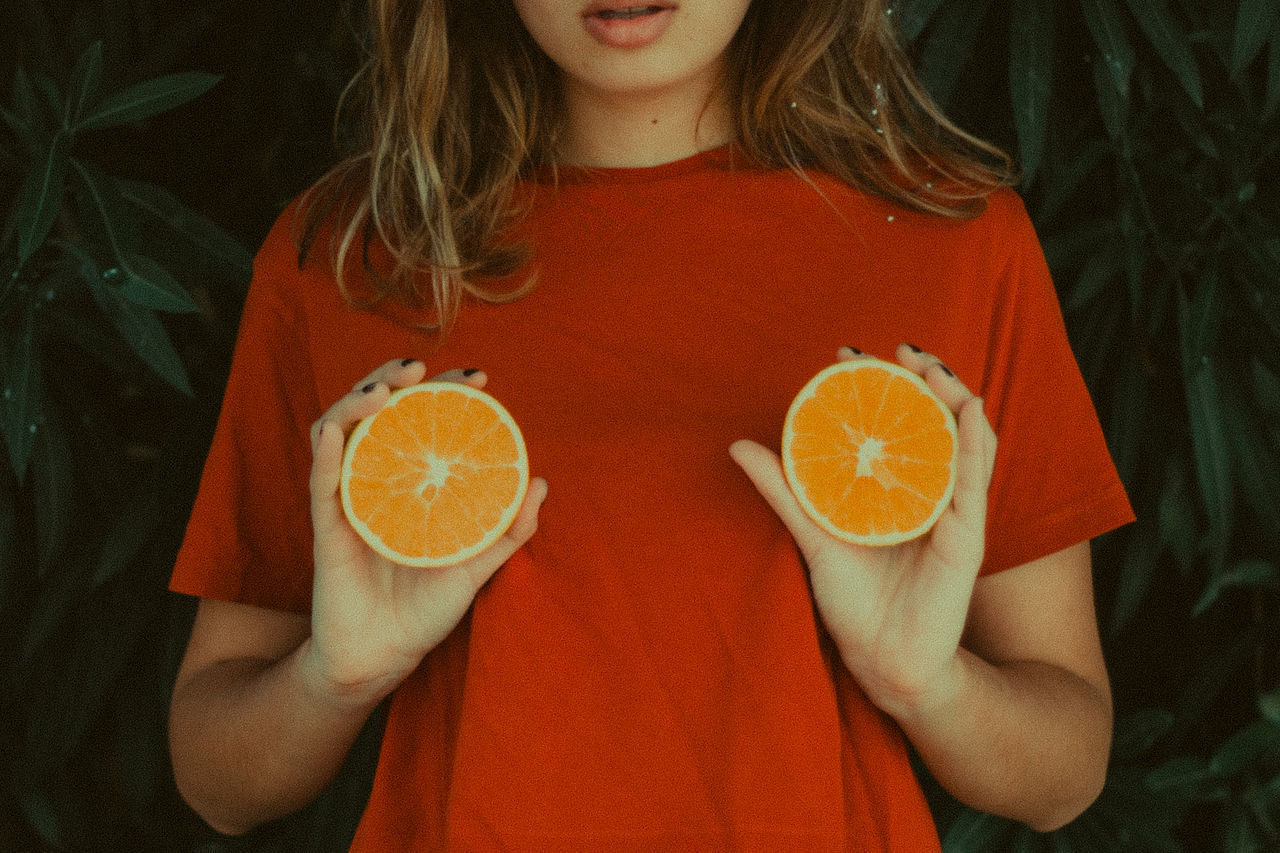 Midsection Of Woman Holding Orange Slices By Plants
