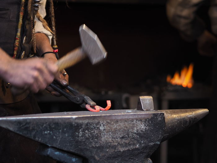 Heat - Temperature Hand Human Hand Fire Burning One Person Flame Blacksmith  Work Tool Holding Fire - Natural Phenomenon Tool Workshop Real People Human Body Part Working Occupation Hammer Indoors  Preparation  Skill  Metal Industry Hitting Iron - Metal