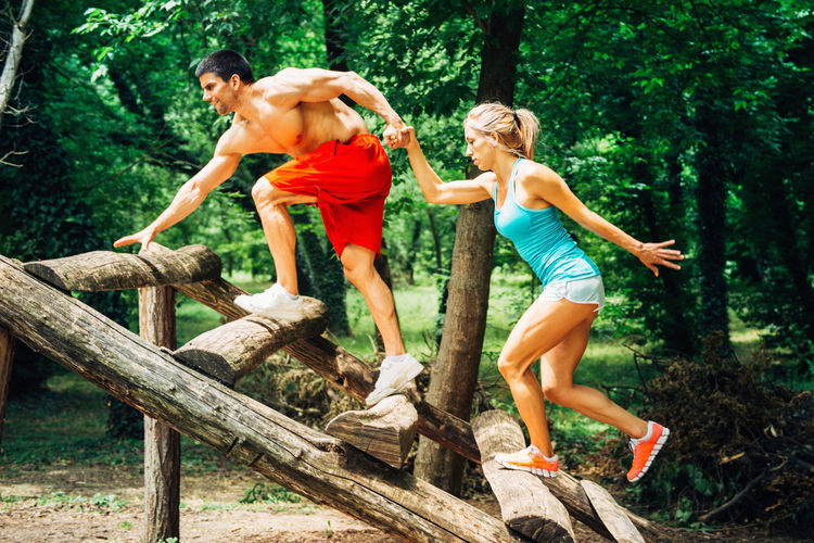 Moving Up On Fitness Trail Outdoors Exercising Young Couple Fitness Training Sport Training Muscular Build Physical Activity Nature Green Park Attractive Couple Beautiful Couple Moving Up Fun Togetherness Wood - Material Fitness Trail Blonde Woman Man Helping Two People