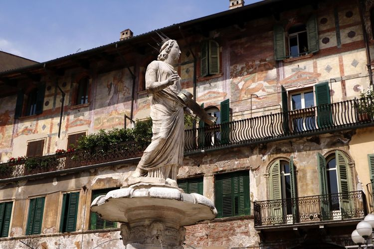 The roman statue Madonna Verona (AD 380) tops the fountain (AD 1368) in the Piazza delle Erbe in Verona, Italy Architecture Sculpture Building Exterior Statue Built Structure Human Representation Representation Art And Craft Low Angle View Window Building Creativity No People History Day The Past Female Likeness Nature Craft Outdoors Travel Travel Photography Travel Destinations Tourist Destination European Architecture
