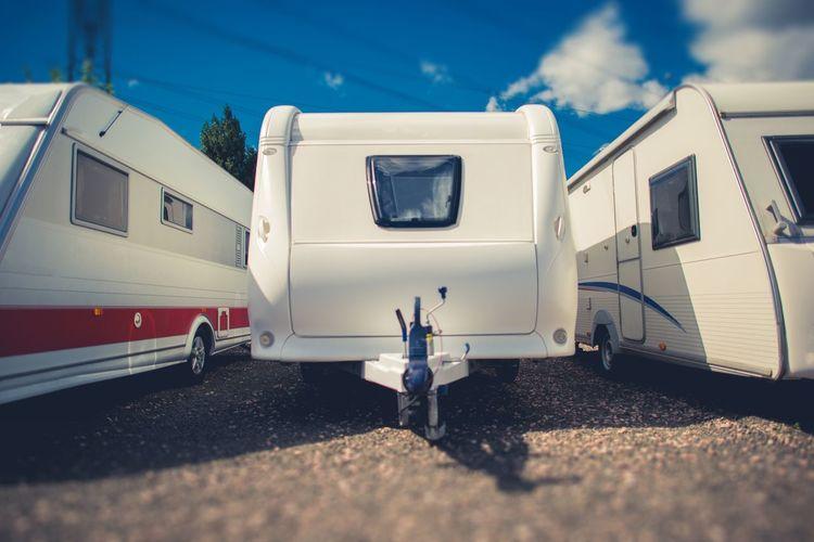 Tilt-shift image of white vehicle trailers against sky
