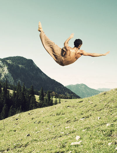 Low angle view of man jumping on mountain