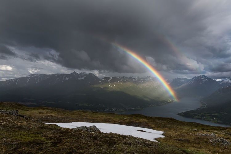 Scenic view of rainbow over mountains during stormy weather