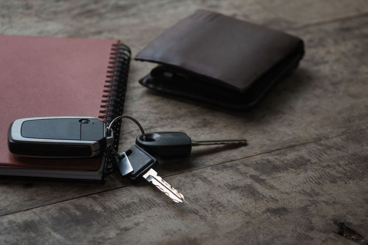 High angle view of diary with wallet and car key on wooden table