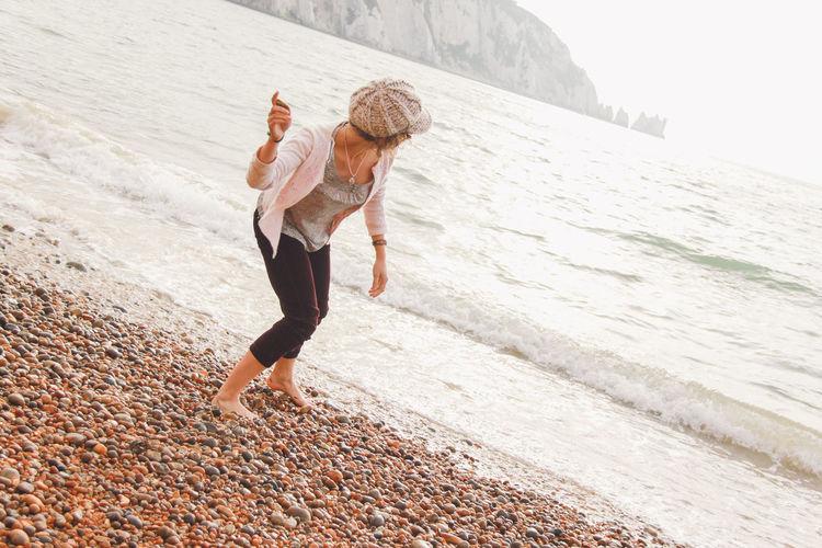 Woman Throwing Pebble In Sea