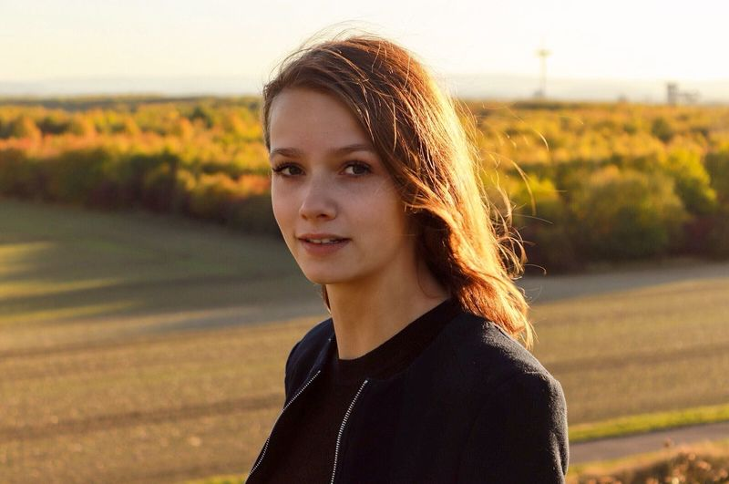Portrait of young woman standing on field
