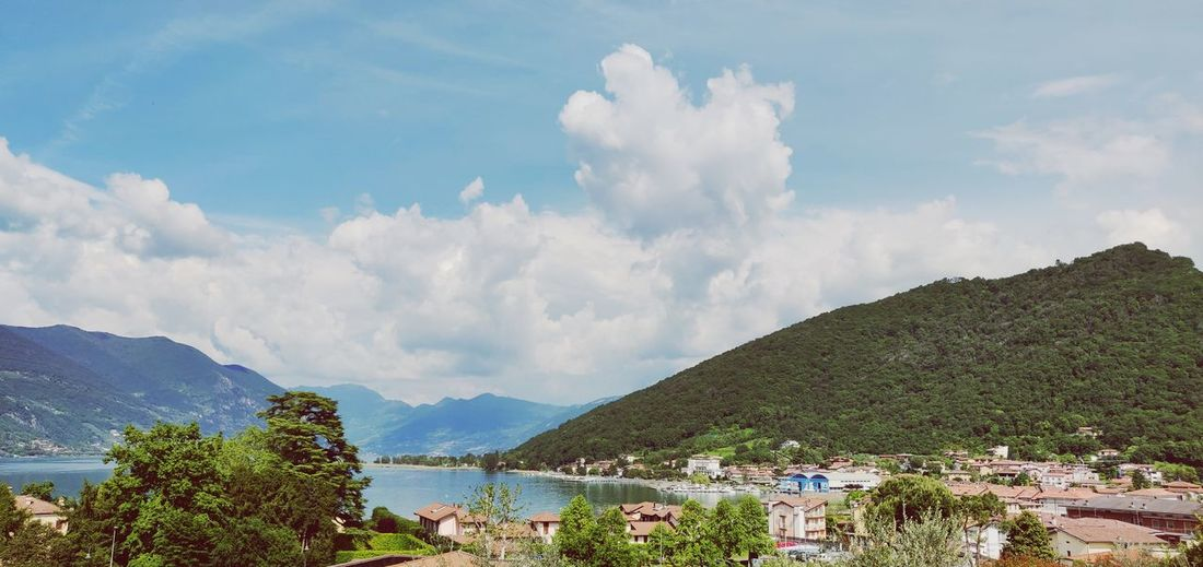 Panoramic view of town by mountains against sky