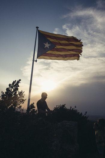 Silhouette of man holding flag against sky