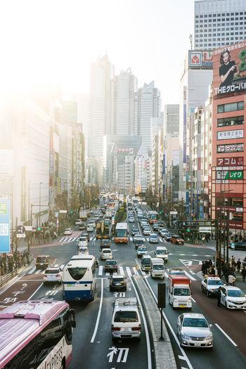 Traffic on city street amidst buildings against sky
