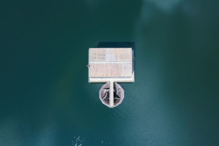 High angle view of information sign on lake against wall