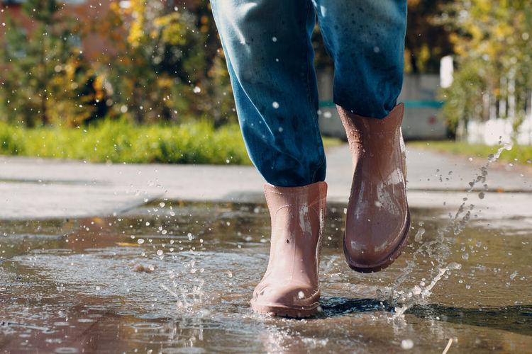 Low section of man splashing water in rain