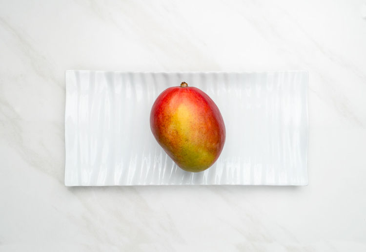 High angle view of apple on table against white background