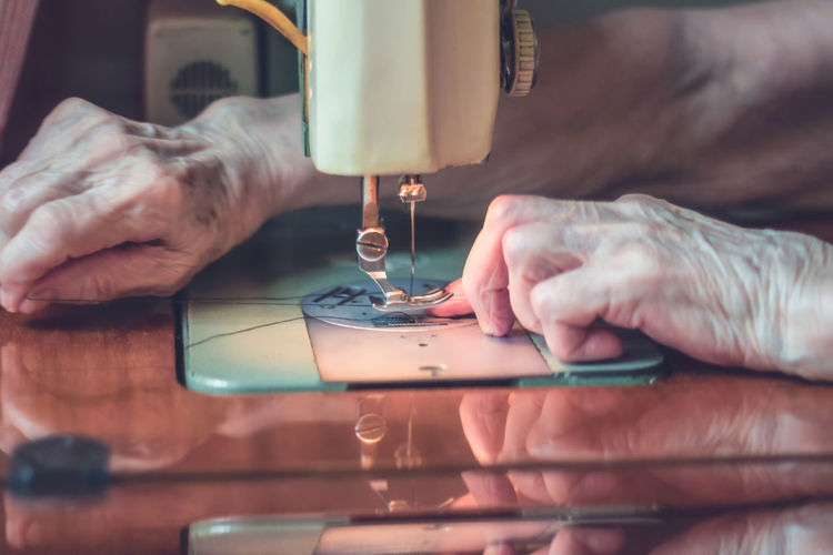 Sewing Machine Human Hand Sewing Working Creativity Art And Craft One Person Textile Real People Skill  Adult Equipment Manufacturing Equipment Tailor Sewing Needle Close Up Woman Wrinkled Senior Adult Elderly Seamstress Occupation
