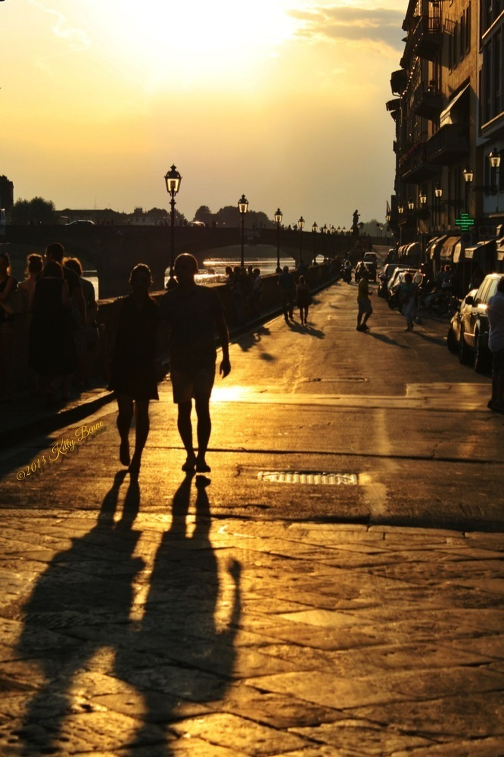 sunset, lifestyles, walking, silhouette, men, person, large group of people, leisure activity, beach, orange color, sunlight, sky, sea, city life, mixed age range, shadow, full length, sun, togetherness