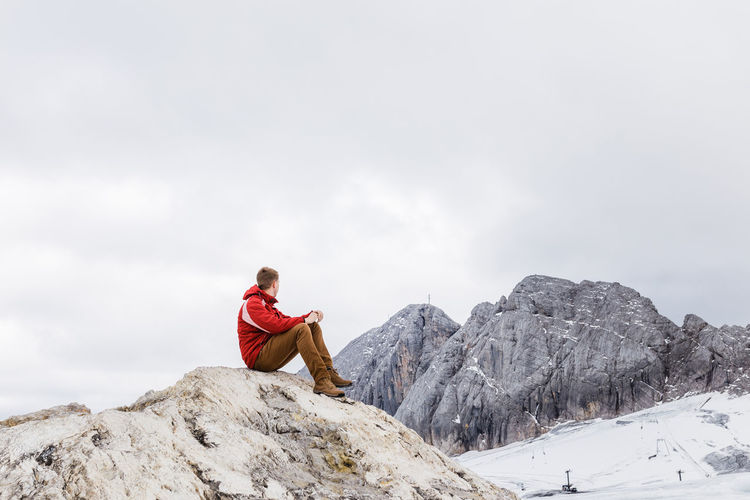 Man sitting on rock by mountain against sky