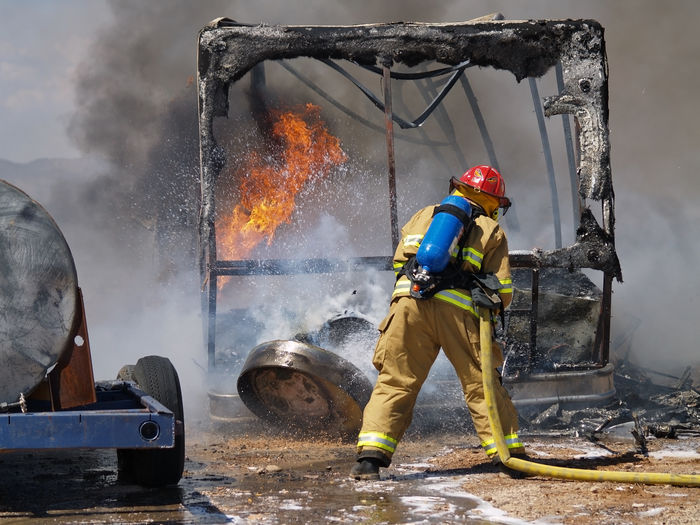 A firefighter battling to put out an intense fire of a burning Recreational Vehicle in Arizona. The firefighter is not facing the camera so no model release is necessary. Arizona Accidents And Disasters Burning Fire Fire - Natural Phenomenon Fire Hose Firefighter Flame Full Length Headwear Heat - Temperature Helmet Men Occupation Outdoors Protection Protective Workwear Real People Rescue Worker Safety Security Smoke - Physical Structure Spraying Water Working