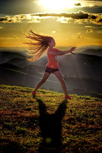 Woman Exercising On Grass At Sunset