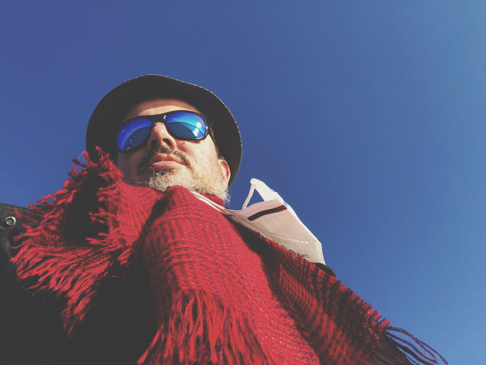 Low angle view of man wearing sunglasses against sky during winter
