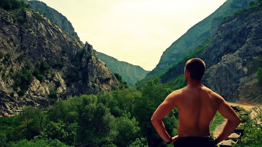 Rear view of shirtless man standing on mountain against clear sky