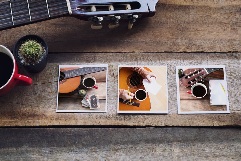 High Angle View Of Guitar With Photographs On Table