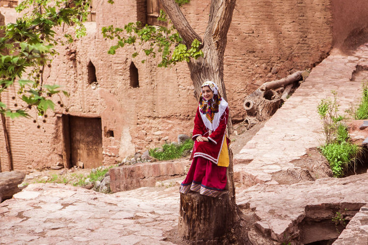 Woman wearing traditional clothes sitting by tree trunk