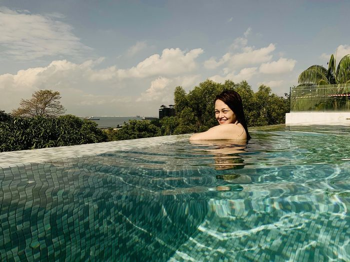 Side view portrait of smiling woman in infinity pool